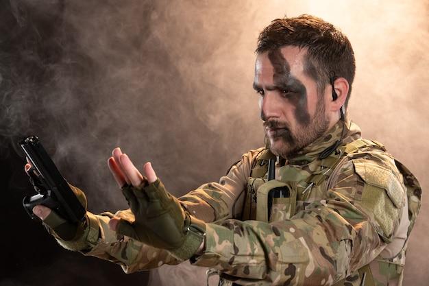 연기가 자욱한 어두운 벽에 항복하는 위장에 남성 군인