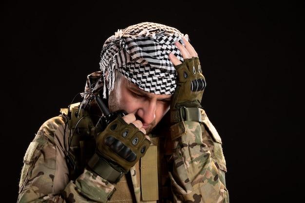 검은 벽에 무전기를 통해 얘기하는 위장에 남성 군인