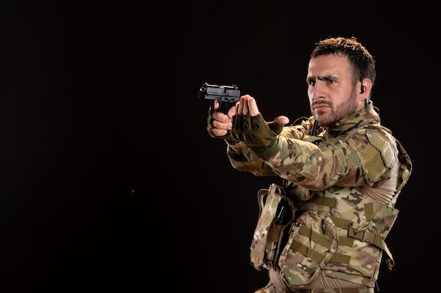 黒い壁に銃を持った迷彩の男性兵士