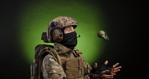 広角で撮影された黒で隔離の暗い背景に武器を持つミリタリードレスの男性兵士
