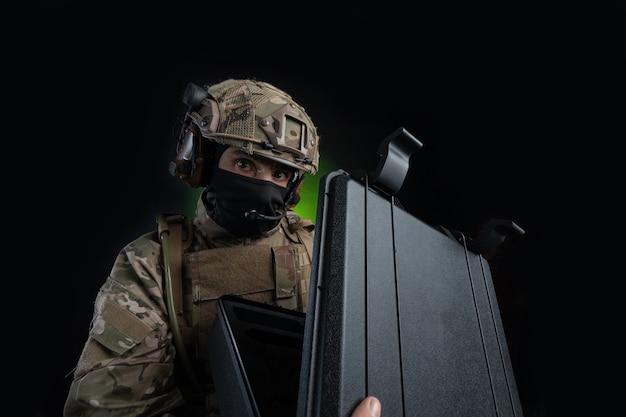 광각으로 촬영된 검정색으로 격리된 어두운 배경에 무기를 든 군복을 입은 남성 군인