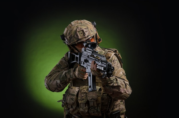 A male soldier in military clothes with a weapon on a dark background