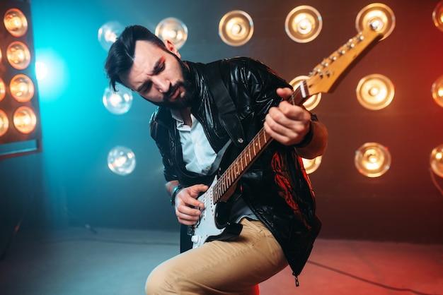 ライトの装飾が施されたステージにエレクトロギターを持つ男性のソロミュージシャン。