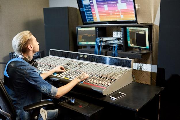 Male sound engineer editing soundtracks