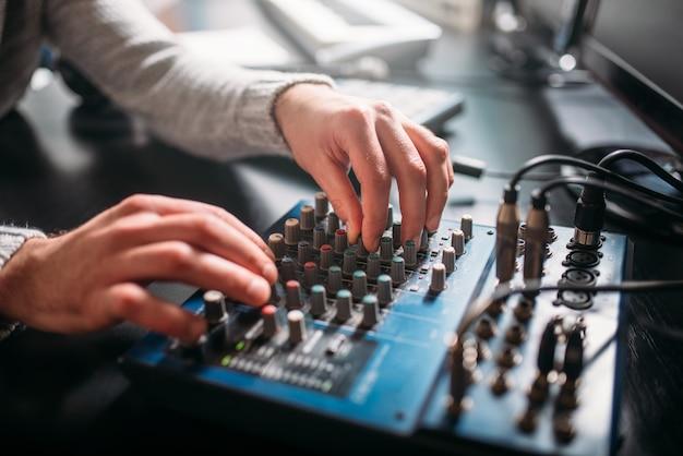 Male sound engineer hands on volume control panel. digital music record studio.