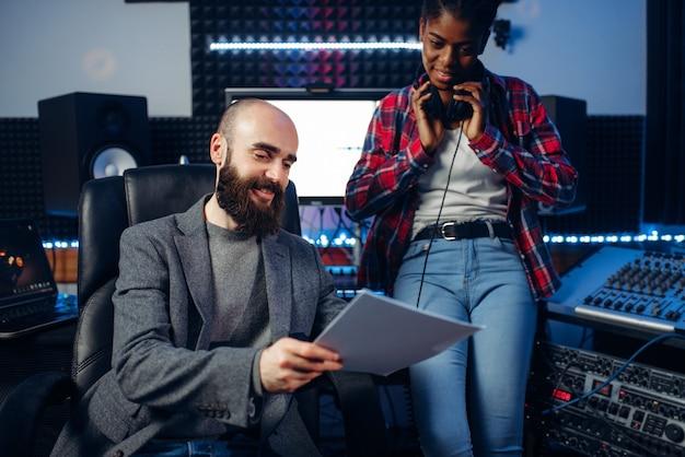 男性のサウンドプロデューサーとヘッドフォンの女性歌手がレコーディングスタジオで作曲を聴いています。プロのオーディオと音楽のミキシングテクノロジー