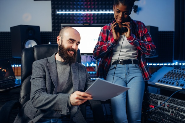Male sound producer and female singer in headphones listens composition in recording studio. professional audio and music mixing technology