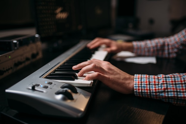 Male sound producer hands on musical keyboard, closeup. digital audio recording technology.