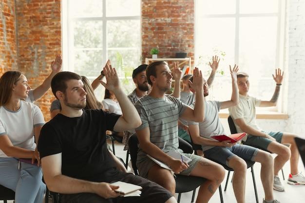 大学のワークショップでホールでプレゼンテーションを行う男性スピーカー。聴衆または会議場。質問をしている学生は、興味を持っているように見えます。学会イベント、トレーニング。教育。