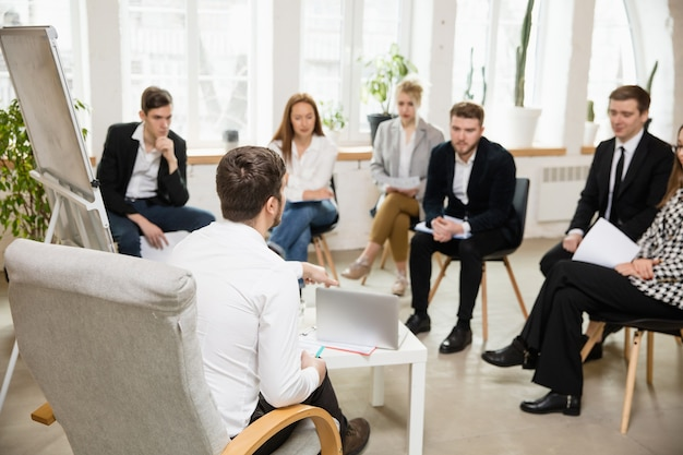 워크숍 청중이나 회의장에서 프레젠테이션을 하는 남성 연사