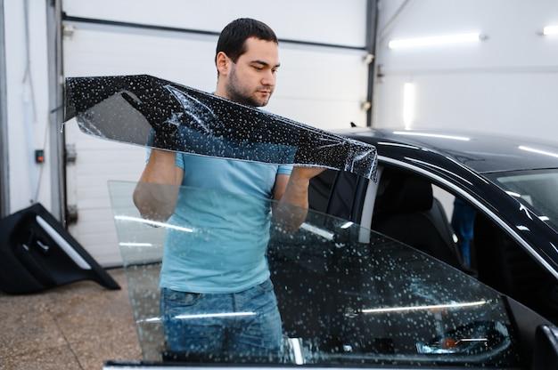 男性スペシャリストがウェットカーの着色、チューニングサービスをインストールします。ガレージの車の窓にビニールの色合いを塗る整備士、色付きの自動車ガラス