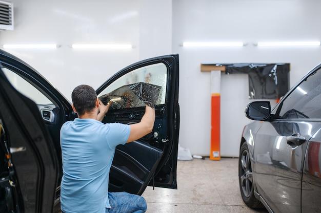 男性スペシャリストがウェットカーの着色、チューニングサービスをインストールします。ガレージの車の窓にビニールの色合いを塗る整備士