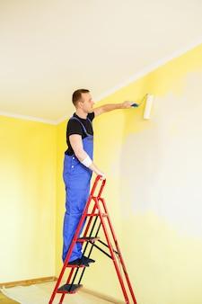 男性の専門家が屋内で壁をペンキで塗ります、修理の概念