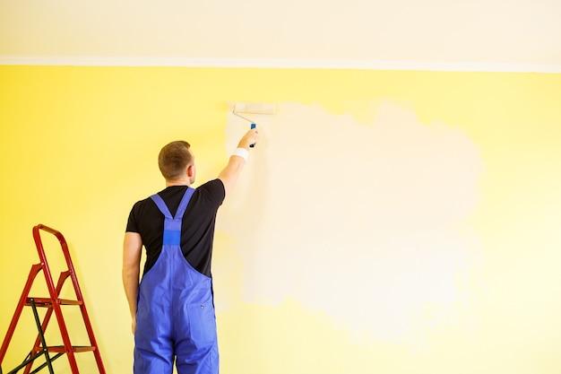 Мужской специалист красит стены краской в помещении, концепция ремонта