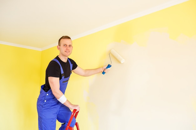 Male specialist paints the wall with paint indoors, repair concept
