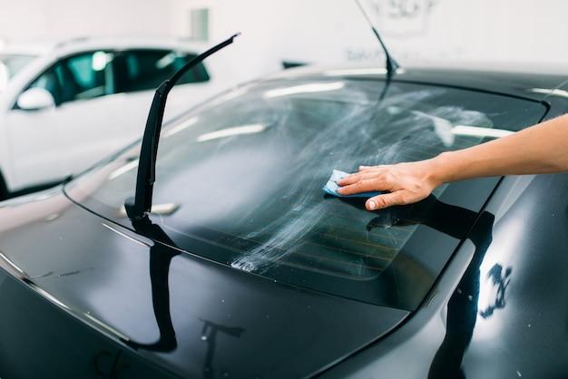 男性の専門家が窓の準備、車の着色フィルムの取り付けプロセス、取り付け手順、