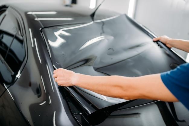 手に車の着色フィルムを持つ男性のスペシャリスト。取り付けプロセス、着色された自動ガラスの取り付け手順
