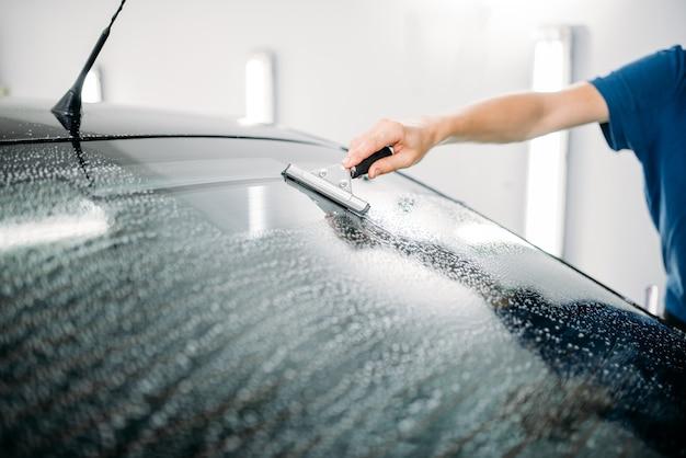 男性の専門家は、窓、車の着色フィルムの取り付けプロセス、取り付け手順、