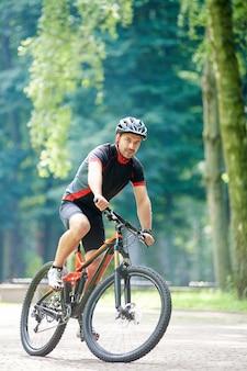 Мужчина-спортсмен, езда на велосипеде на открытом воздухе
