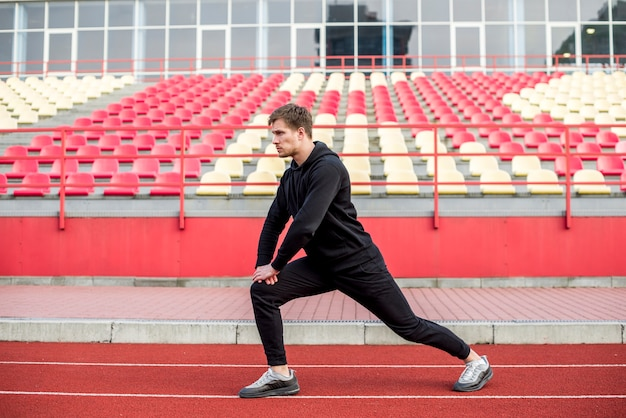 Male sportsperson exercising on race track in front of bleacher