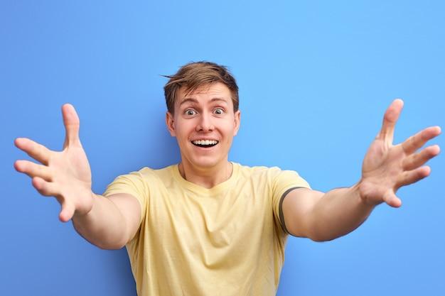 男性は腕を広げ、抱きしめ、カメラに向かって微笑み、前向きな感情を表現し、身振りで示す。孤立した青い背景