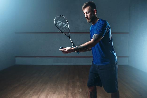 Мужской игрок в сквош с тренировкой с ракеткой на крытом корте.