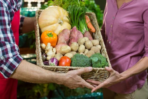 Мужской персонал помогает женщине с покупками продуктов
