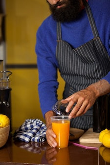 Male staff closing the lid of juice glass at counter