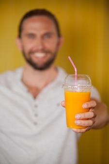 Male staff holding orange juice glass at organic section