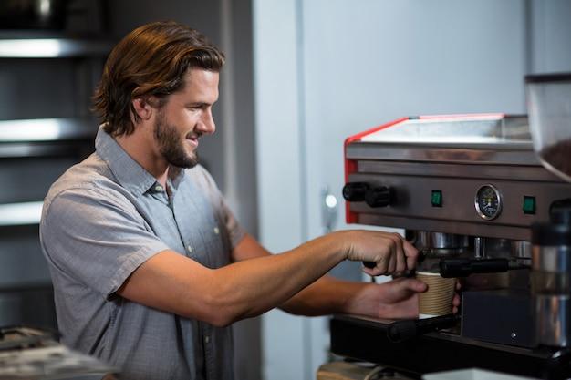 Мужской персонал, заваривающий чашку кофе за стойкой