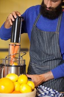 Male staff preparing juice at organic section