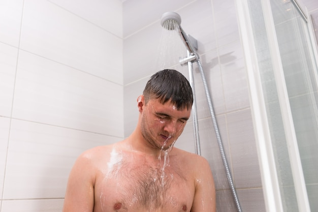 Male standing under flowing water in shower cabin with transparent glass doors in the modern tiled bathroom