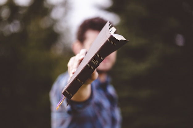 Maschio in piedi e che tiene un libro in mano