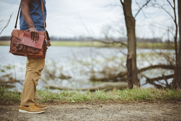 Мужчина стоит возле озера, держа библию