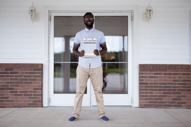 Мужчина стоит возле церкви, держа волонтер в буфер обмена