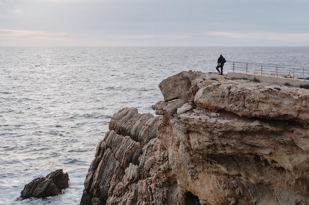 Мужчина стоит на скале и наслаждается живописным видом на закат