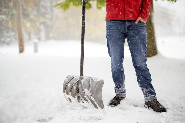 Мужчина стоит на заснеженном поле и держит лопату для снега
