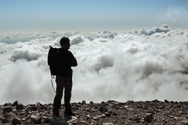 Мужчина стоит на вершине горной вершины