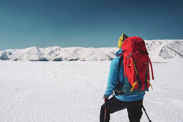 ルーマニアの雪に覆われたカルパティア山脈の息をのむような景色を見つめる男性