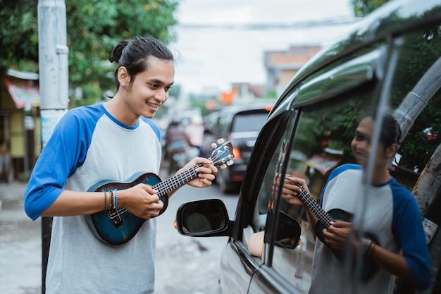 Male street musician begging for money from traffic light
