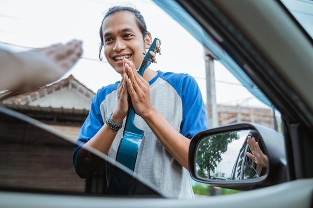 Male street musician begging for money