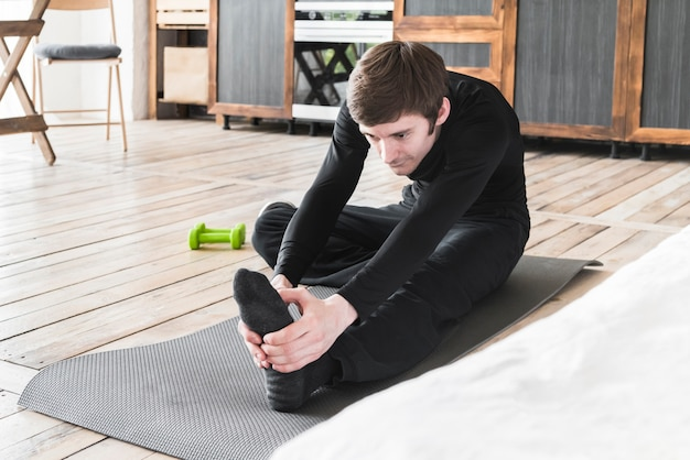 Male stretching legs on exercise mat