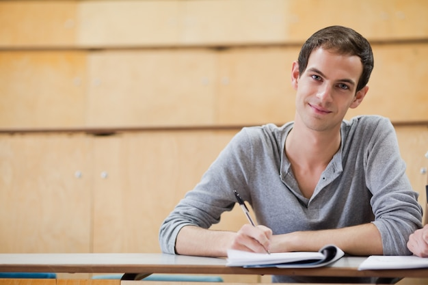 Male student holding a pen