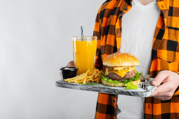 Male student is holding board with a fresh burger.