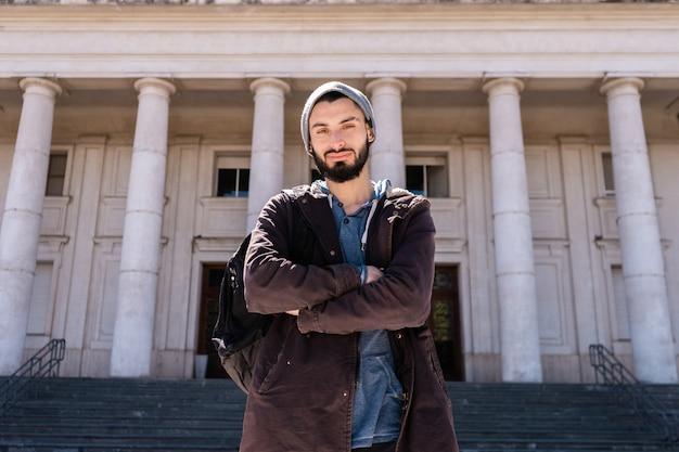 Студент, стоящий перед зданием университета