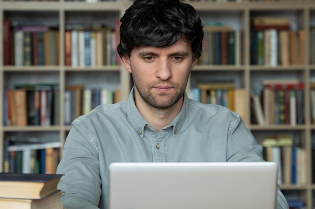 Студент, использующий ноутбук, учится в библиотеке университета