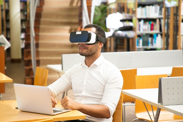 Male student using vr headset during work in library
