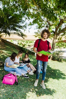 Male student with book standing near friends