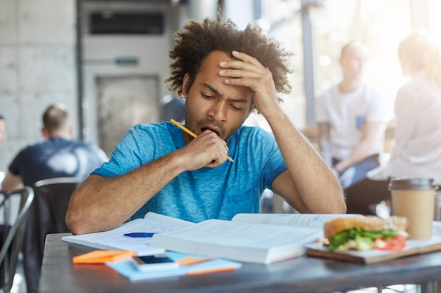 Studente maschio con un bel raccolto di capelli e setole seduto alla mensa universitaria a bere caffè e mangiare fast food essendo esausto