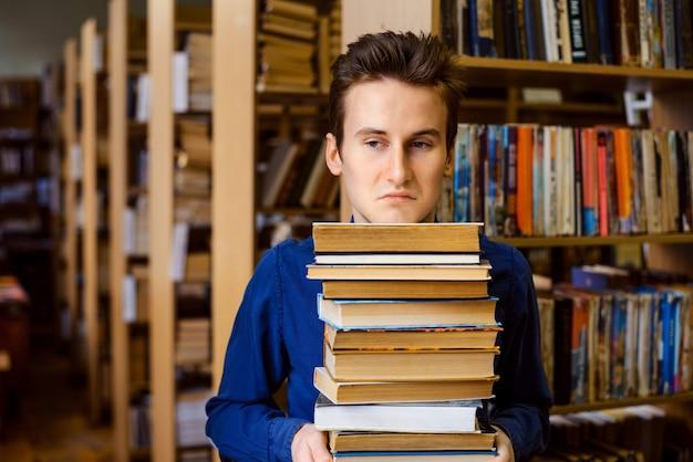 Студент с негативной и скучающей мимикой на лице держит большую стопку книг в библиотеке